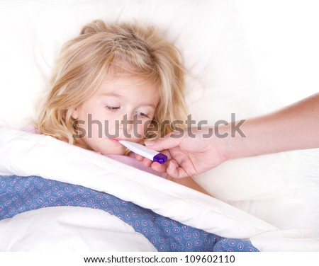 sick child with a thermometer in mouth lying in bed - stock photo