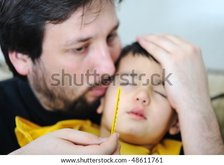 Sick child, with focusing on thermometer in father's hand - stock photo
