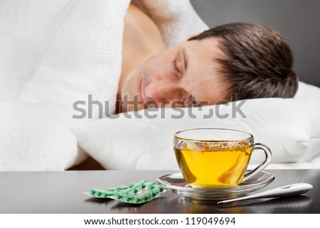 sick cold man lying in bed with fever,  cup of herbal tea, pills and thermometer in the foreground, focus on tea cup - stock photo
