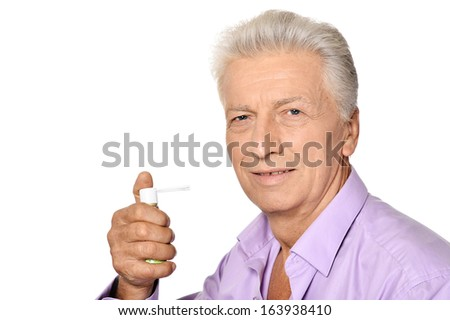 Sick elderly man with inhaler on white background