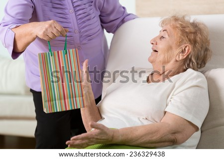 Sick elderly woman getting the gift from her old good friend - stock photo