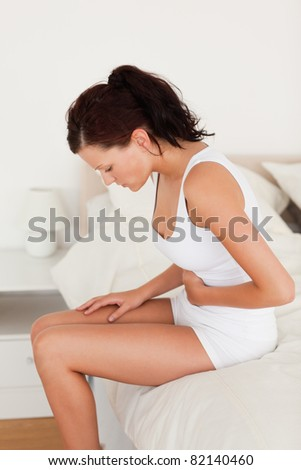 Sick feeling woman sitting on her bed in her bedroom