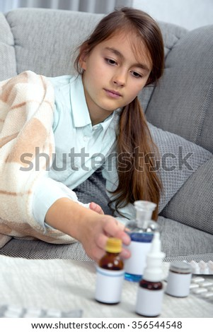Sick girl  in sofa with medications on a bedside table