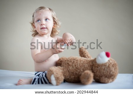 Sick girl is sitting on the bed with teddy-bear