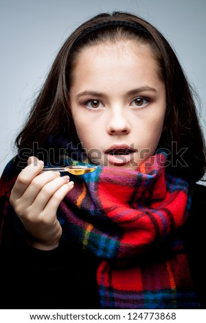 sick girl is taking cough syrup. medicine - stock photo