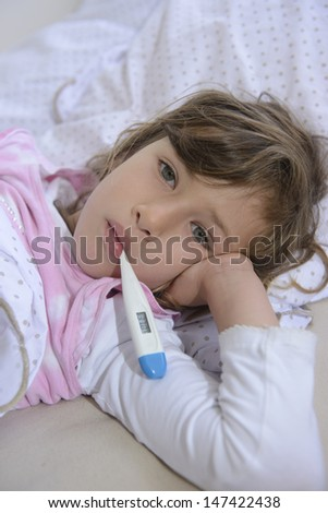sick girl lying in bed measuring fever - stock photo