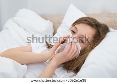 Sick Girl On Bed Sneezing In Handkerchief In Bedroom - stock photo