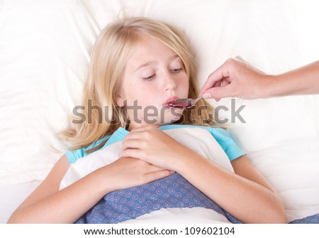Sick girl taking medicine from a spoon laying in bed - stock photo