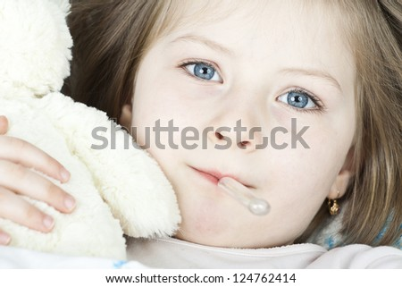 Sick girl with a thermometer and teddy bear lying in bed - stock photo