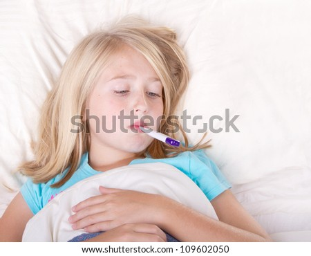 sick girl with a thermometer in mouth lying in bed - stock photo