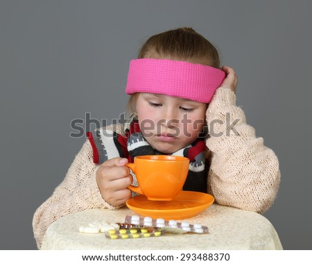 Sick in headband girl sits near table with medicine pills and drinks tea from orange cup on gray background - Treatment, cold or disease concept - stock photo