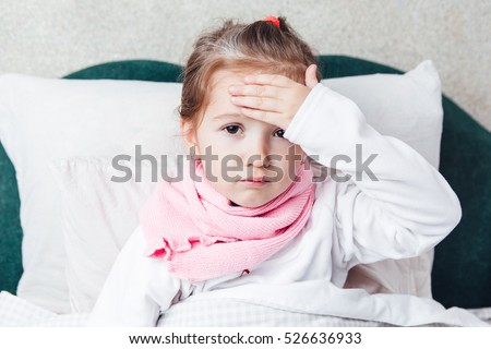 Sick kid lying in the bed and touch her forehead