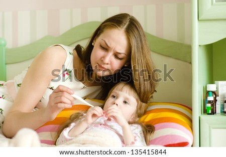 Sick kid with high fever laying in bed and mother taking temperature - stock photo