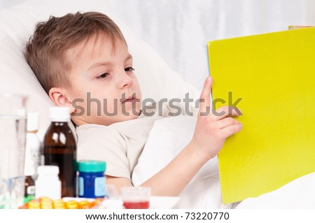 Sick little beautiful boy with book in the bed - stock photo