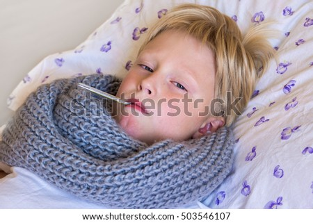 Sick little boy holding thermometer laying in bed with sad face - healthcare and medicine concept
