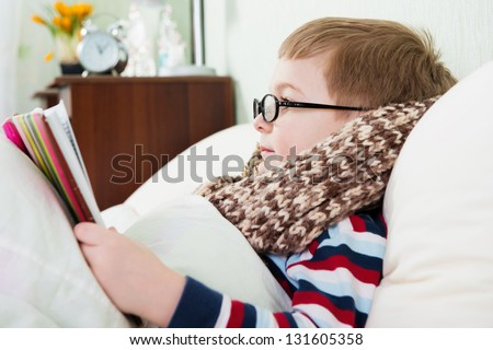Sick little boy in glasses lying in bed with book - stock photo