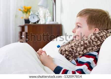 Sick little boy lying in bed with thermometer in mouth - stock photo