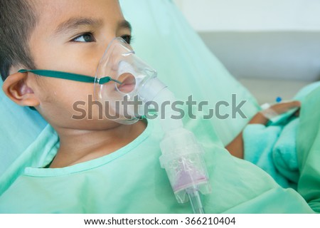 sick little boy makes inhalation in hospital room. - stock photo