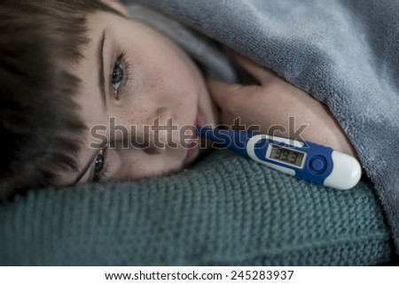 sick little boy with thermometer in his mouth