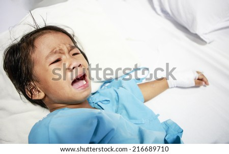 Sick little girl crying in hospital bed - stock photo