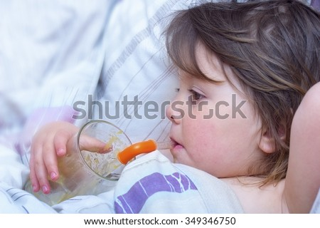 Sick little girl drink juice through a straw in a bed - stock photo