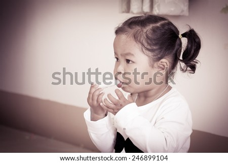 Sick little girl giving medicine syringe by herself in vintage style - stock photo