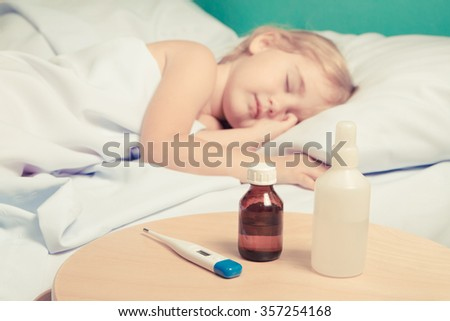 Sick little girl in bed.Virus, flu, cold, fever.( focus on the cure) - stock photo