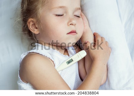 Sick little girl in bed with a thermometer - stock photo