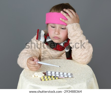 Sick little girl in headband sits near table with medicine pills and looks at thermometer on dark gray background - Treatment, high temperature, cold or disease concept - stock photo