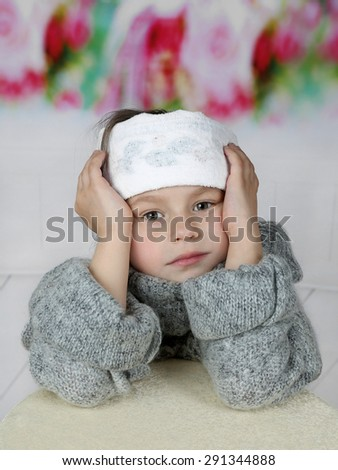 Sick little girl in headband sitting sad - stock photo