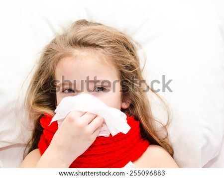 Sick little girl lying in the bed and blowing her nose