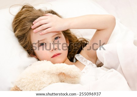 Sick little girl lying in the bed with her toy