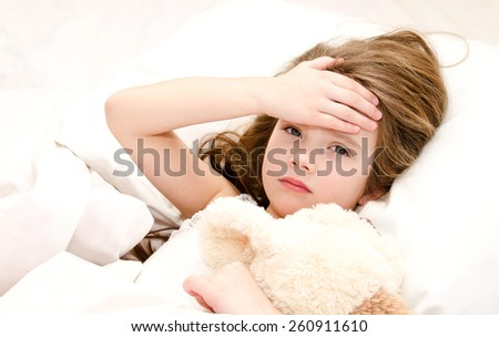 Sick little girl lying in the bed with her toy - stock photo
