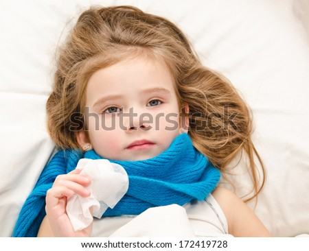 Sick little girl lying in the bed with scarf and tissue for blowing nose - stock photo