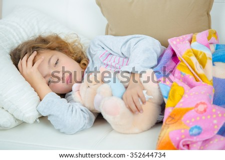 Sick little girl on the sofa with a fever - stock photo