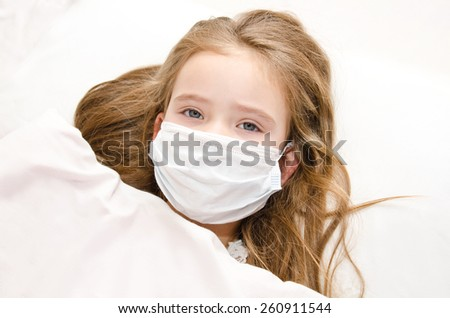 Sick little girl with surgical face mask for bacterial and virus flu protection in the bed - stock photo