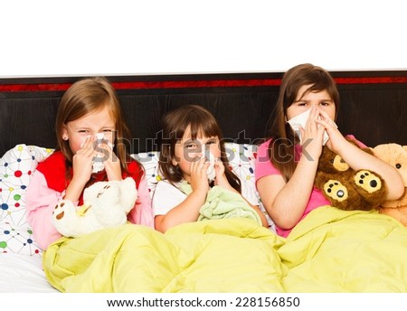 Sick little girls suffering from bad influenza, staying in bed. - stock photo