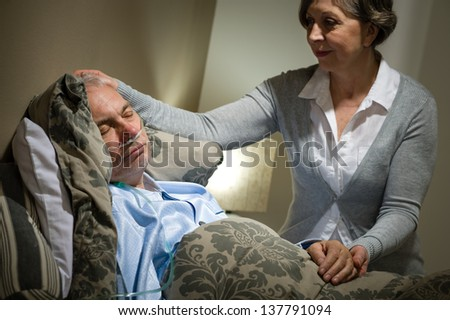 Sick lying senior man with caring wife at home - stock photo