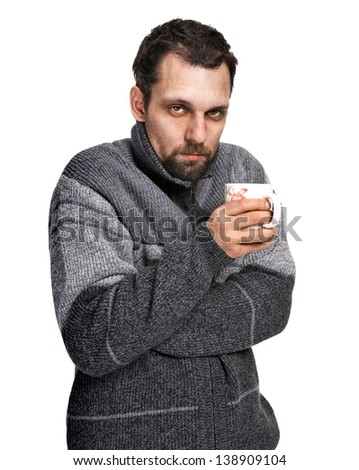 Sick man, affected by cold, dressed in grey sweater holding a cup of tea in hands isolated on white background  - stock photo