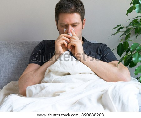 Sick man blowing his nose while lying on bed at home. - stock photo