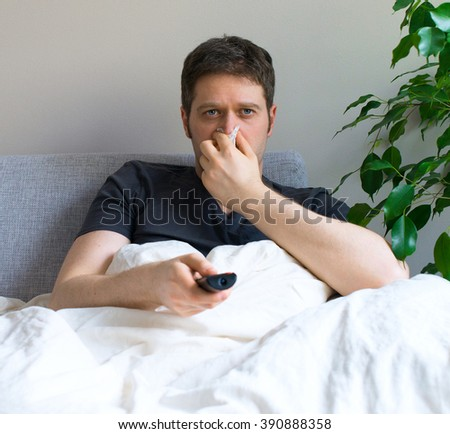 Sick man blowing his nose while watching TV at home. - stock photo