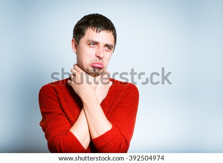 sick man has a sore throat isolated on a gray background - stock photo