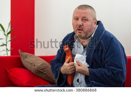Sick man in bed having a headache holding a hot-water bottle - stock photo
