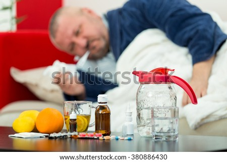 Sick man in bed with drugs and fruit on table - stock photo
