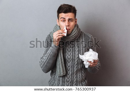 Sick Man in sweater and scarf holding serviette and using spray while looking at the camera over gray background