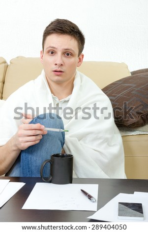 Sick man measuring temperature on thermometer while sitting on sofa at home. Ill male student  having headache covered with white blanket while learning for exam. - stock photo