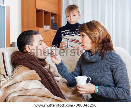 Sick man surrounded by caring wife and  son in living room at home