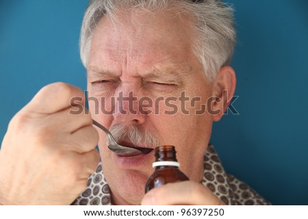 sick man takes a spoonful of cough syrup - stock photo