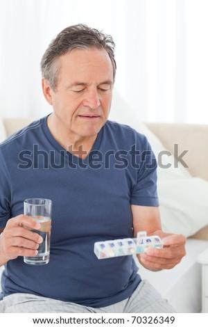 Sick man taking his pills at home - stock photo