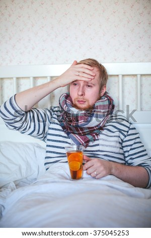 sick man with a scarf drinking hot tea in bed